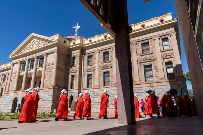 "Protesters dressed as handmaids from the TV show ""The Handmaid's Tale"" rally at the Arizona state Capitol on May 21, 2019, as part of a nationwide effort to protest laws placing extreme restrictions on abortion recently adopted in some states."
