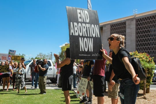 Counterprotesters hold signs as abortion-rights activists gather at a rally to protest abortion bans at Arizona State Capitol in Phoenix on May 21, 2019.