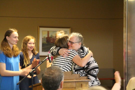 Holly Hockenberry gets a hug from Milton Hershey housemother Tanya Wagner after receiving one of three inaugural Parent/Sponsor of the Year Awards from the school's Family Gratitude Foundation in Honor of Gertrude Gurt.