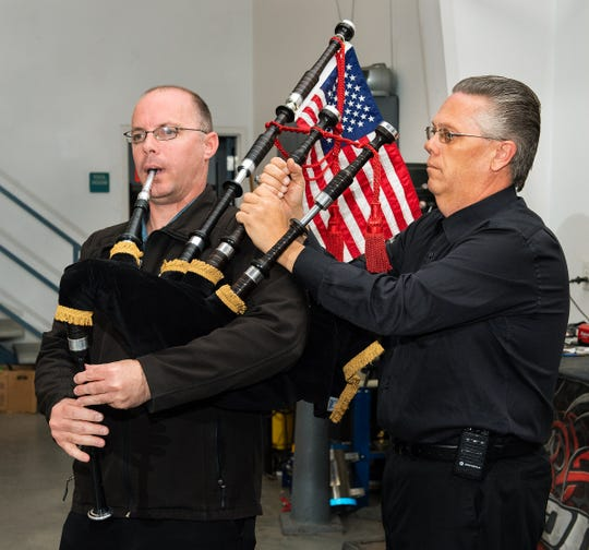Aaron Pellegrini, right, tunes a bagpipe played by Donald McCandless.