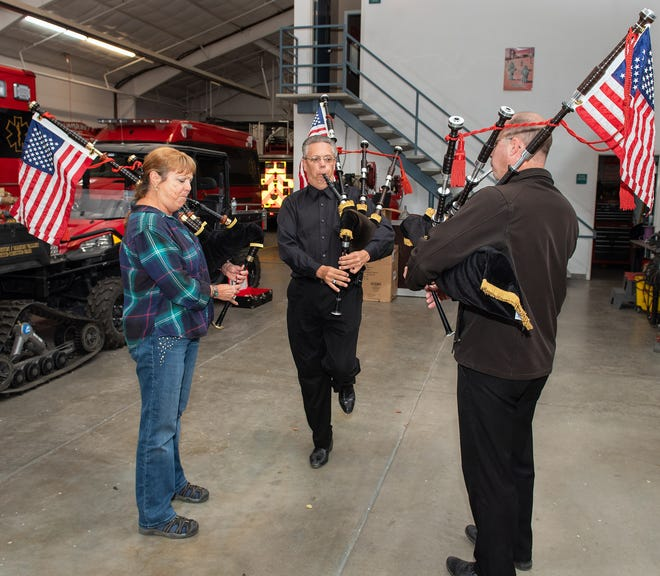 Debbie Pellegrini, Aaron Pellegrini and Donald McCandless, left to right, practice bagpipes inside the fire department building.