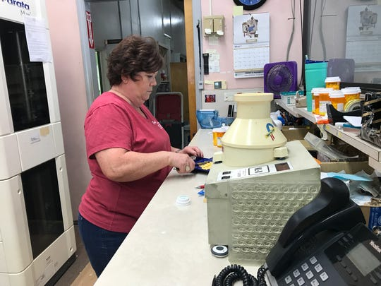 Sandy Brinton, who worked as a pharmacy technician at Ferry's Pharmacy, does inventory on Tuesday afternoon. Ferry's closed last week after nearly 45 years in business.