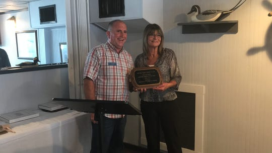 Jeannie Rose is presented the 2019 Business Person of the Year award by Benjy Holloway, president of the Chincoteague Chamber of Commerce Board of Directors, on Monday, May 20, 2019 at Don's Seafood Restaurant in Chincoteague, Virginia.