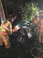 Firefighters work to extricate a trapped motorist after a crash Tuesday, May 21, at around 3 a.m. in the woods off Salisbury Bypass.