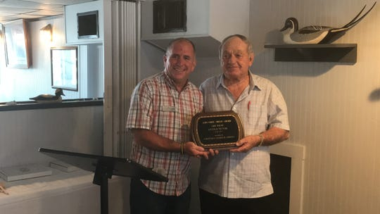 Gary Mason, right, is presented the 2019 Citizen of the Year award by Benjy Holloway, Chincoteague Chamber of Commerce Board of Directors President on Monday, May 20, 2019 at a luncheon at Don's Seafood Restaurant in Chincoteague, Virginia.