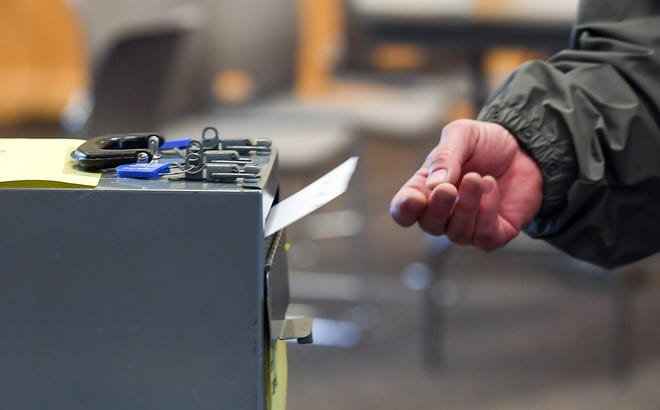 A voter submits his ballot for the school board election Tuesday, May 21, in Sioux Falls.