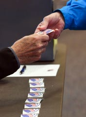 """A poll worker gives an """"I voted"""" sticker to a voter during the school board election Tuesday, May 21, in Sioux Falls."""