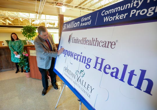 Brooks Miller, the president and CEO of Jordan Valley Community Health Center, places the final puzzle piece on the board during a press conference announcing a $1 million from UnitedHealthcare on Tuesday, May 21, 2019.