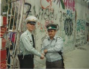 """Gregg Bursey, left, shakes hands with an East German Border Guard in front of the East Berlin side of the Berlin Wall in 1990. Bursey later titled the photo, """"What Wall?"""""""