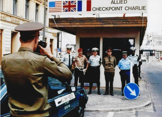 A Soviet Officer takes a photo of Gregg Bursey, far left, with two American military policemen, a British military policeman, a Soviety officer and a French officer outside Allied Checkpoint Charlie in June 1990. The photo of the moment was captured by a reporter for the Berliner Morgenpost, which published it on the front page.