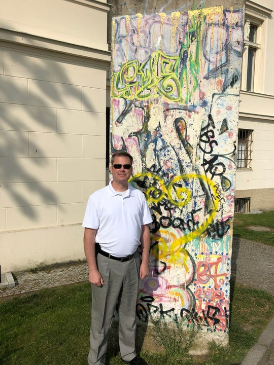 Gregg Bursey poses with a piece of the Berlin Wall during his trip to Berlin with the Checkpoint Charlie Foundation in May 2019. Bursey served as a military policeman in Berlin during the fall of the wall, from 1989 to 1992.