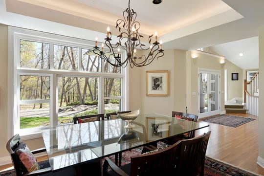 The formal dining room nearby is infused with natural light coming from the large bay window.