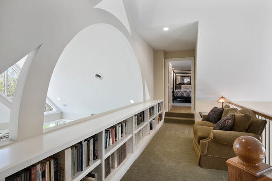 The loft overlooks the main entry to the home and serves as the perfect in-home library with built-in shelves spanning the space.