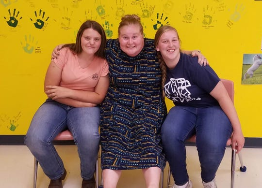 Snow Canyon High School students Avery Macfarlene, left, and Arianna Hafen, at right, flank their FFA advisor and agriculture teacher Tawney Campbell.