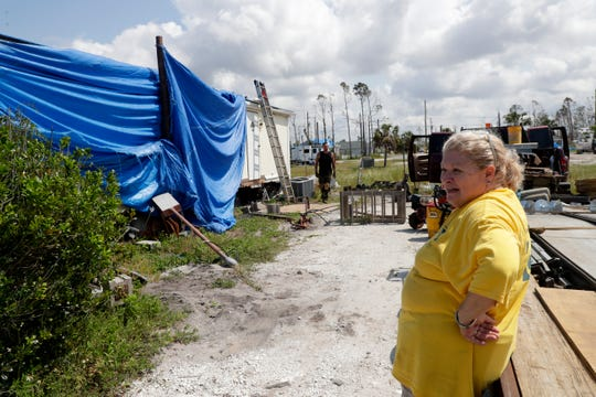 Mexico Beach homeowner Cindy Neal  watches as workers put her home back on cinderblocks after it was pushed off of them during Hurricane Michael.