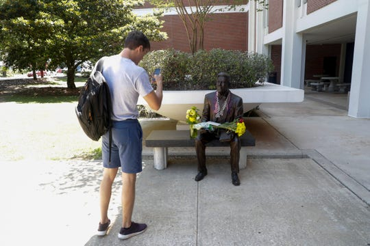 FSU Law School student Chris Hill takes a photo of the statue of Sandy D'Alemberte, former Florida State University president and dean of its College of Law, covered in tributes to him the day after his sudden death, Tuesday, May 21, 2019.