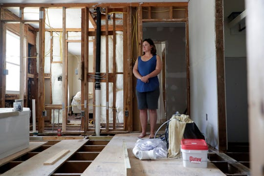 Kim Nobles, a Port St. Joe homeowner, stands on a sheet of plywood where her floor used to be. The home was gutted due to water damage from Hurricane Michael seven months ago.