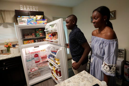 Deontae Cromartie, 13, left, and his sister Treniyah Cromartie, 14, open their fridge to find it fully stocked with food and beverages Tuesday, May 21, 2019.