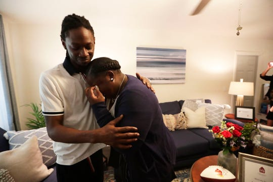 Marvin Williams, left, hugs his sister Jessica Williams, right, as she cries tears of joy after entering her home to find it fully furnished Tuesday, May 21, 2019. Williams' home was built with assistance from Habitat for Humanity and furnished by Aaron's.