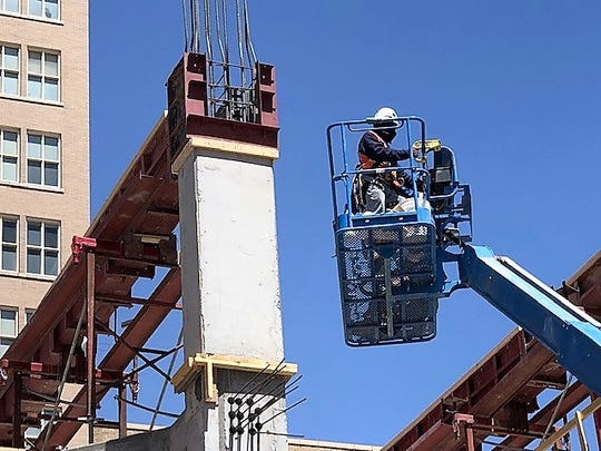 A worker is helping construct the parking garage next to the Plaza Hotel building, which is being renovated into a boutique hotel. Construction is one of the industries adding jobs in El Paso, and helping to reduce this area's unemployment rate to a historic low.