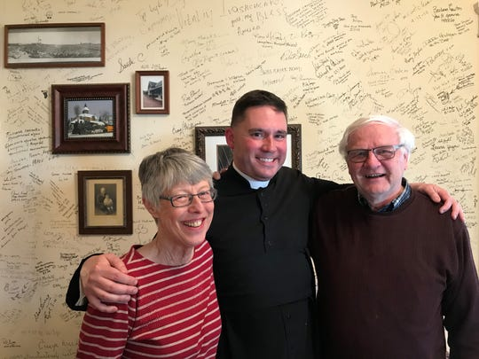 Lori Torkko, left, with The Rev. Canon Aaron Huberfeld, center, and Dave Torkko, right, in front of a wall in the entrance hall at the Everest Inn. Guests signed their name on the wall so the Torkkos could preserve the memories.