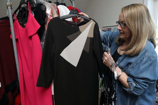 Diane Sussman, one of the founders for Center for Safety & Change, shows some of the designer pieces from the annual fashion sale fundraiser May 21, 2019 at the center's office in New City.