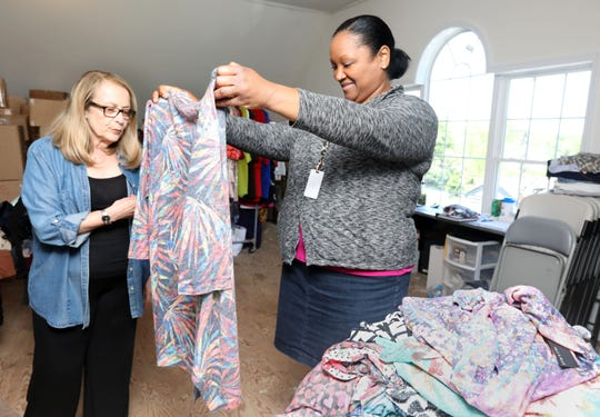 Tracie McLee, right, director of development at the Center for Safety & Change, looks at a tunic with Diane Sussman, one of the center's founders, as they go though items for the annual fashion sale fundraiser May 21, 2019 at the center's office in New City.