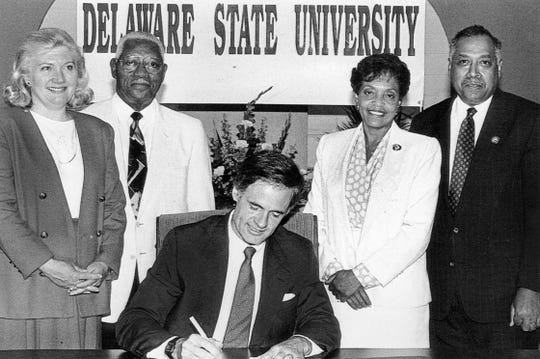 On July 1, 1993, Gov. Tom Carper signs Senate Bill 138, which changed Delaware State College to Delaware State University. Looking on, from left, are Representative Nancy Wagner, Senator Herman Holloway Sr., Vermell DeLauder and President William B. DeLauder.
