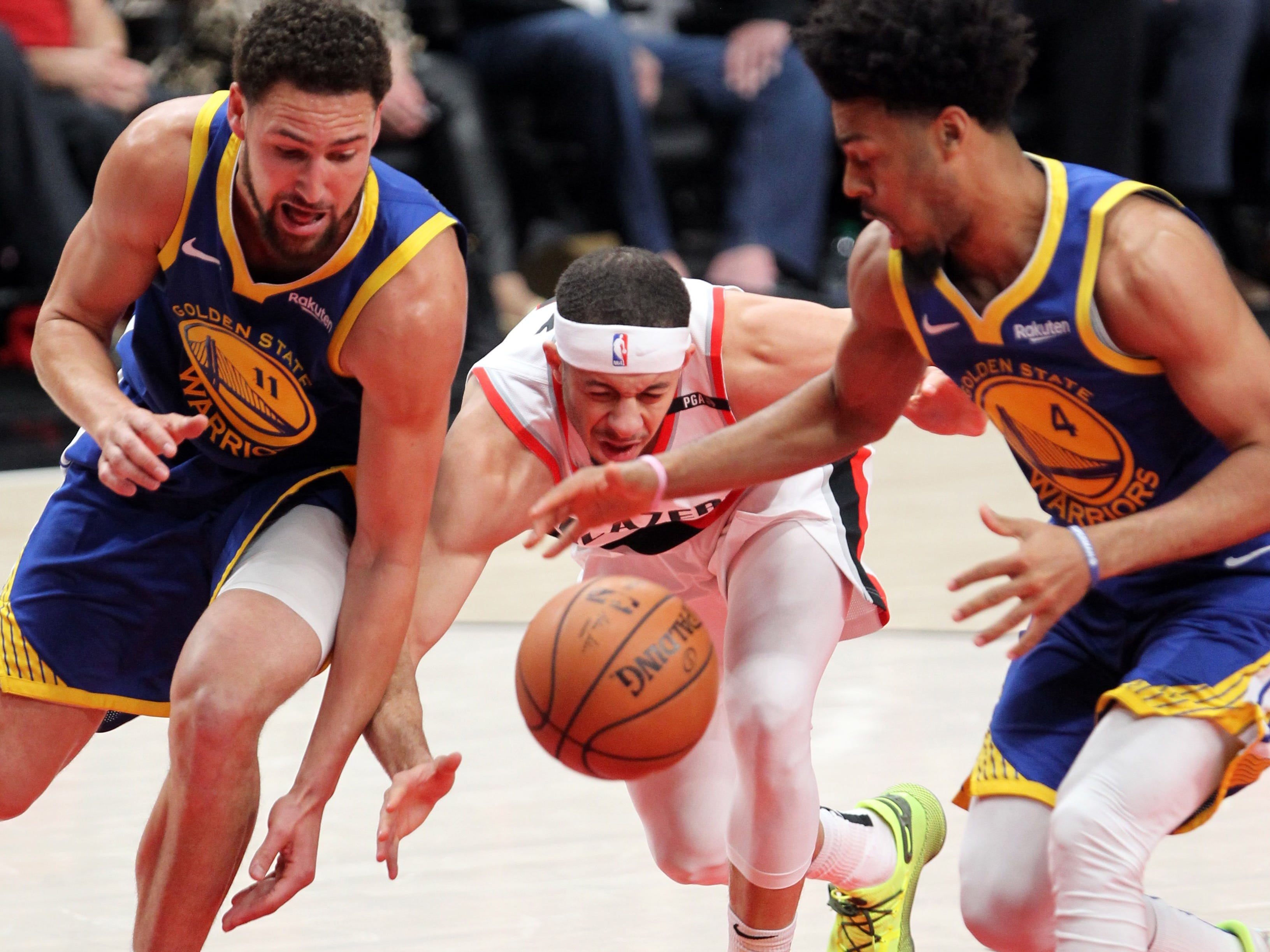 May 20: Golden State Warriors guards Klay Thompson (left) and Quinn Cook strip the ball from Portland Trail Blazers guard Seth Curry in the first half of Game 4.