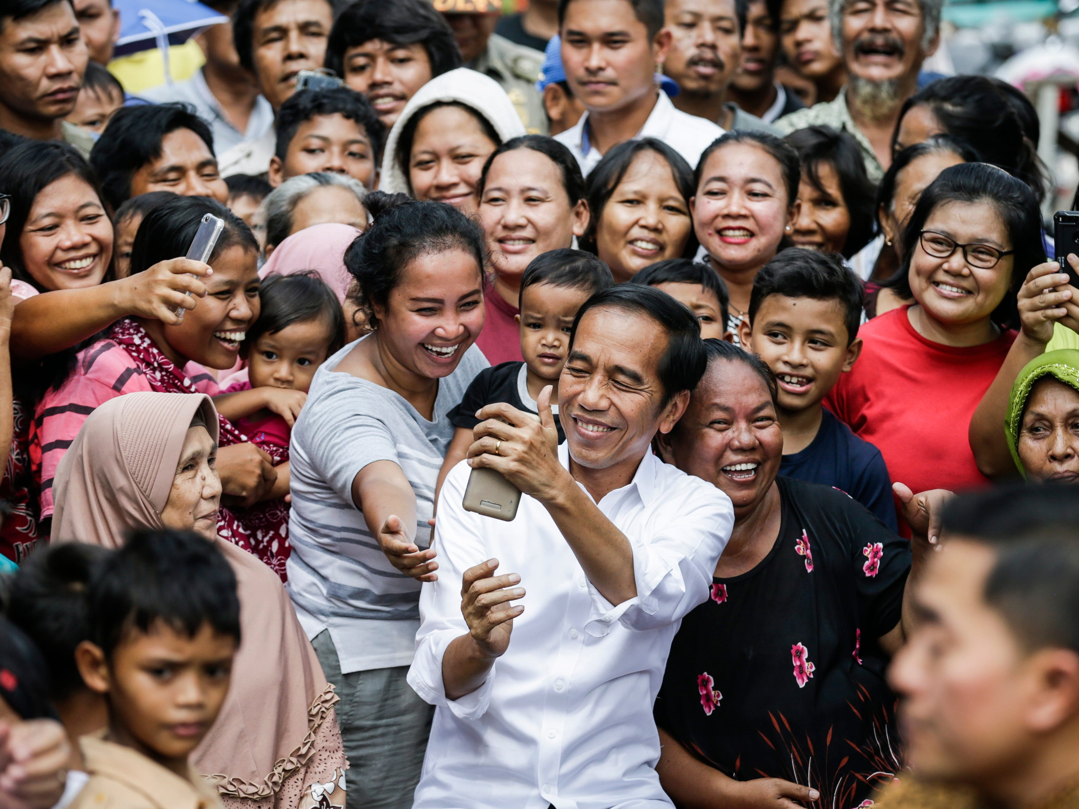 Indonesia's Incumbent President from the Indonesian Democratic Party of Struggle (PDIP) Joko Widodo (C) takes a selfie photograph with local residents after his victory speech following the announcement of the election results at a slum area in Jakarta, Indonesia, May, 21, 2019. Incumbent Indonesian President Joko Widodo was re-elected after winning the presidential election over his rival, retired General Prabowo Subianto, the election commission announced early on May 21, 2019.