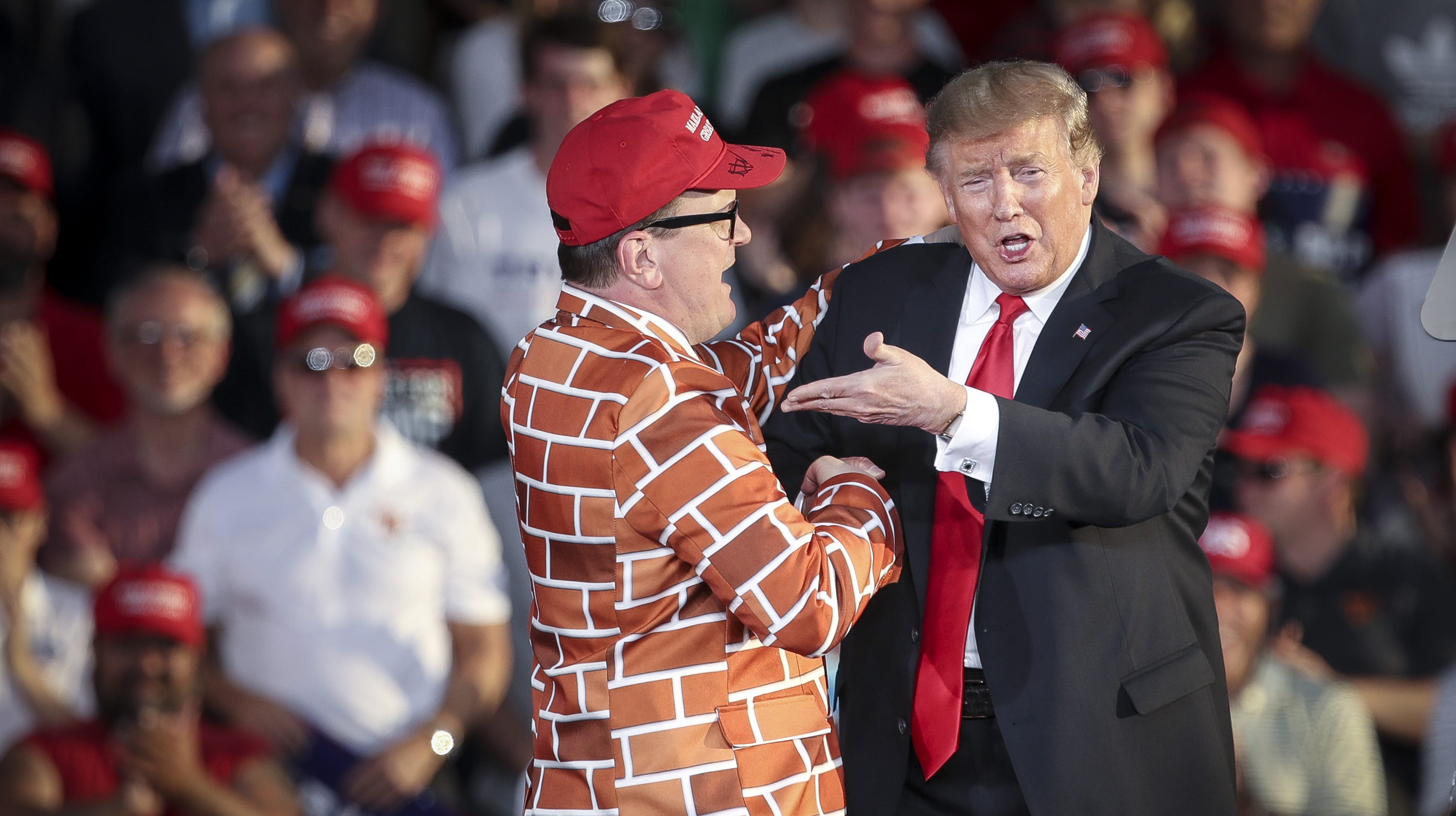 MONTOURSVILLE, PA: President Donald Trump calls up Blake Marnell, wearing a jacket with bricks representing a border wall, to the stage during a 'Make America Great Again' campaign rally at Williamsport Regional Airport on May 20 in Montoursville, Pennsylvania. Trump is making a trip to the swing state to drum up Republican support on the eve of a special election in Pennsylvania's 12th congressional district, with Republican Fred Keller facing off against Democrat Marc Friedenberg. (Photo by Drew Angerer/Getty Images) ORG XMIT: 775341208 ORIG FILE ID: 1145317959