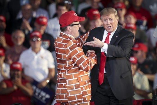 President Donald Trump calls up Blake Marnell, wearing a jacket with bricks representing a border wall, to the stage during a 'Make America Great Again' campaign rally at Williamsport Regional Airport on May 20 in Montoursville, Pennsylvania.