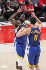 Golden State Warriors forward Draymond Green celebrates with guard Klay Thompson after making a 3-pointer in overtime of Game 4.