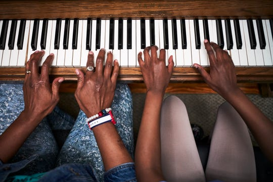 Danielle Scott plays the piano with her daughter Juliánne Arruda during a piano lesson after school in Baton Rouge, Louisiana.