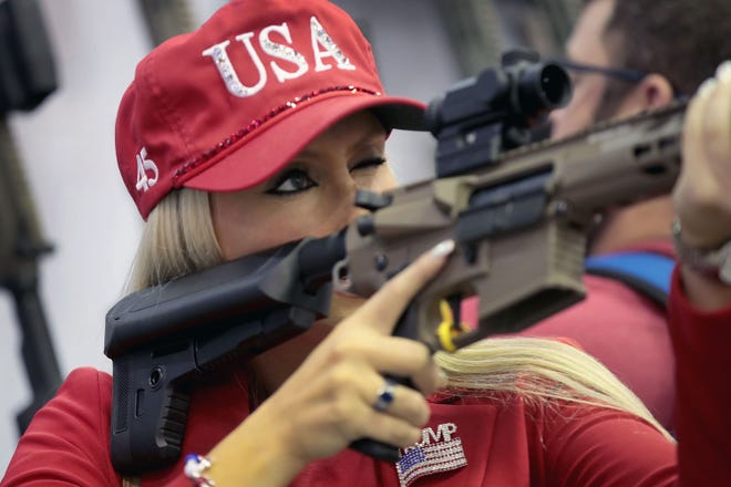 Keleigh Glover examines a rifle scope at the National Rifle Association's 148th annual convention in Indianapolis in April. The group is among those pressing the Supreme Court for major changes in Second Amendment rights.