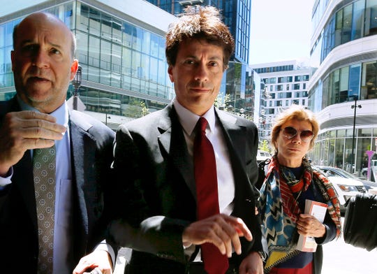 Agustin Huneeus, center, arrives at federal court Tuesday, May 21, 2019, in Boston, where he is scheduled to plead guilty to charges in a nationwide college admissions bribery scandal. (AP Photo/Michael Dwyer) ORG XMIT: BX101