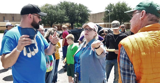 Mary Cooksey, of 2-1-1 Texas, gives instructions to volunteers who gathered Saturday afternoon in the parking lot of Pioneer Drive Baptist Church (background) to begin post-tornado relief efforts.