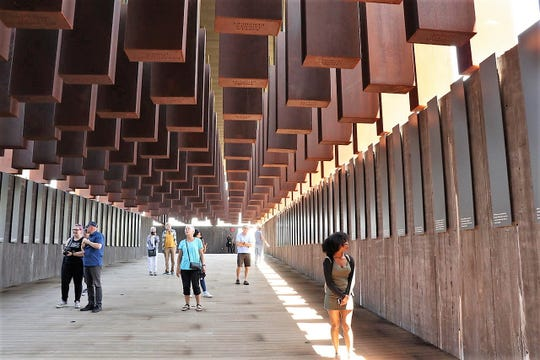 Visitors to the National Memorial for Peace and Justice in Montgomery, Alabama, walk below steel columns that represent people who were lynched.