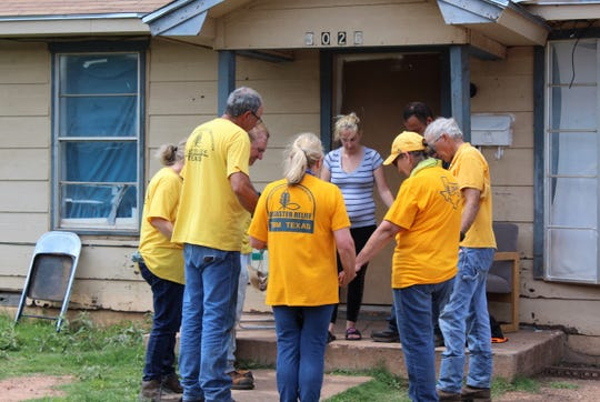 Members of Texas Baptist Men, including women, pray with a couple outside their South Second Street home after helping to clear tornado damage.