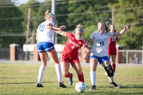 Hendersonville's Eden Hawkins (4) moves the ball past two defenders in the Western Championship game against Lake Norman Charter School on May 21, 2019, at Hendersonville High School. (www.BlueRidgeExpressions.com)