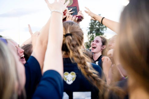 Roberson senior Hope Ingram holds the WNC regional trophy as the Rams celebrate their 5-3 overtime win over Northern Guilford May 21, 2019.