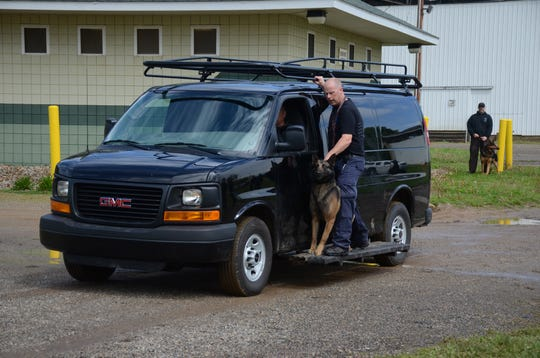 Battle Creek officer Kevin Farnham and his dog Bruizer ride on the side of a van as part of training held in Marshall this week.