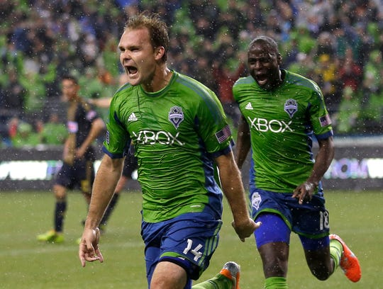 FILE - In this May 3, 2014, file photo, Seattle Sounders' Chad Marshall (14) celebrates with teammate Djimi Traore after Marshall scored the game-winning goal in the second half of an MLS soccer match against the Philadelphia Union, in Seattle. Three-time MLS defender of the year Chad Marshall has announced his retirement due to injury, bringing an end to a 16-year career that included stints with the Columbus Crew and Seattle Sounders. Marshall announced his decision Wednesday, May 22, 2019, after missing Seattle's last two games with knee inflammation.