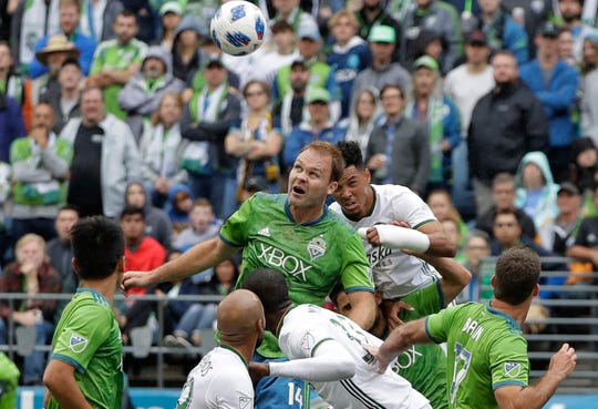 FILE - In this June 30, 2018, file photo, Seattle Sounders' Chad Marshall, center left, and Portland Timbers' Julio Cascante, center right, battle for a header in the first half of an MLS soccer match, in Seattle. Three-time MLS defender of the year Chad Marshall has announced his retirement due to injury, bringing an end to a 16-year career that included stints with the Columbus Crew and Seattle Sounders. Marshall announced his decision Wednesday, May 22, 2019, after missing Seattle's last two games with knee inflammation.