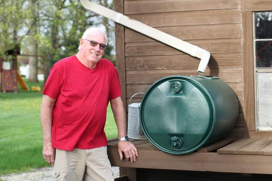 Rick and Dianna Zaebst garden together, including planning for water storage when water is needed for their vegetables. Rick stands with one of the two homemade rain barrels on their property in Bucyrus.