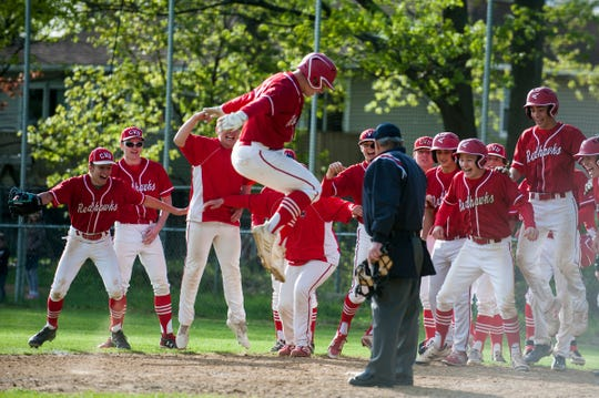 CVU's Aidan Johnson (4) leaps to tag home plate as he is greeted by his teammate after hitting a home run during the baseball game between the Champlain Valley Union Redhawks and the South Burlington Wolves at South Burlington High School on Tuesday afternoon May 21, 2019 in South Burlington, Vermont.