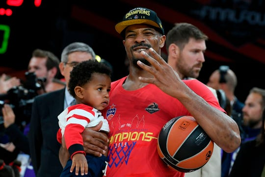 Kyle Hines celebrates his fourth EuroLeague championship while holding his son, Justin.