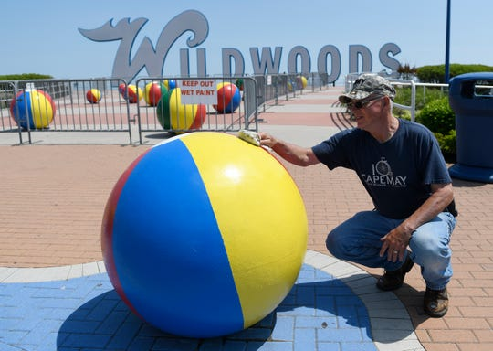 Chuck Hughes, a Wildwood Convention Center maintenance employee, cleans one of the concrete beach balls at Wildwood's boardwalk welcome sign in 2019. The shore town will get a lot of offseason attention when President Trump holds a campaign rally there on Jan. 28.