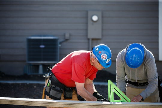 Habitat for Humanity Construction Manager Stephan Baker, right, works with Jim Snodgrass, left, to cut siding for a home that is part of a community of 23 homes near Birdland Marina on Wednesday, May 22, 2019, in Des Moines. The city of Des Moines is updating its zoning code for the first time in more than 50 years, but some of the changes will make it difficult to build affordable housing in Des Moines.