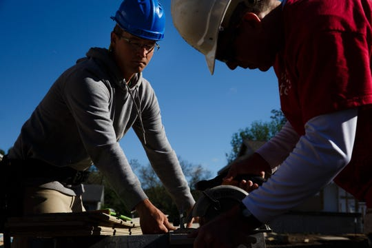 Habitat for Humanity Construction Manager Stephan Baker, left, works with Wells Fargo volunteer Cory Koester, right, to cut siding for a home that is part of a community of 23 homes near Birdland Marina on Wednesday, May 22, 2019, in Des Moines. The city of Des Moines is updating its zoning code for the first time in more than 50 years, but some of the changes will make it difficult to build affordable housing in Des Moines.